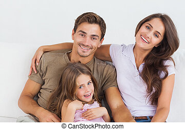 Happy family sitting together on a sofa in the living room