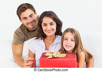 Parents offering a gift to their daughter