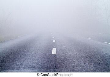 Asphalt road in an autumn fog
