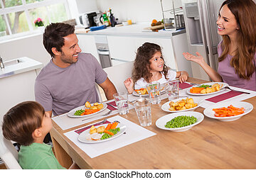 Family talking around the dinner table in kitchen