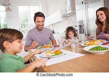 Family smiling around a good meal in kitchen