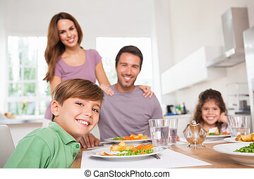 Family looking at the camera at dinner time in kitchen