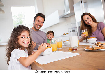 Family smiling at the camera at breakfast