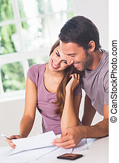 Smiling lovers in front of invoices in house