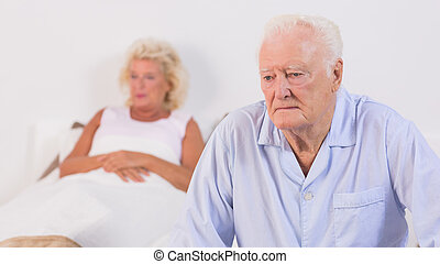 Unsmiling aged couple in the bedroom