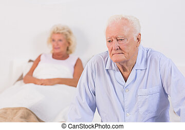 Unsmiling old couple in the bedroom