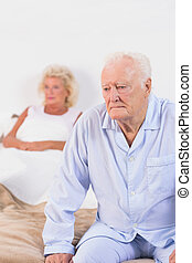 Elderly couple on a bed - Serious elderly couple on a bed
