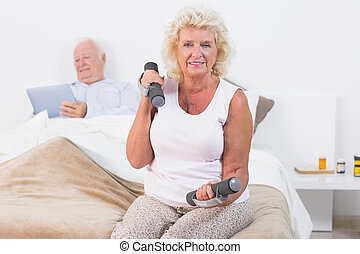 Elderly woman exercising with hand weights sitting on the...