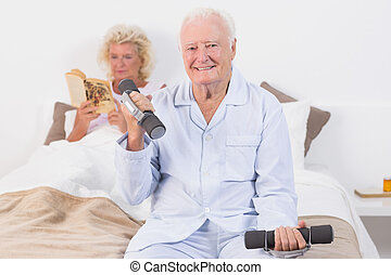 Elderly man lifting hand weights in the bedroom