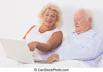 Old couple using a laptop on the bed