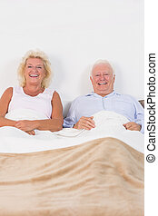 Aged couple lying on the bed and smiling