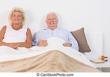 Old couple lying on the bed and smiling