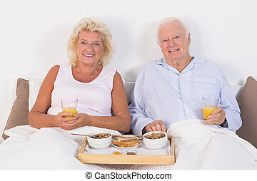 Aged couple eating breakfast lying on the bed