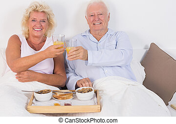 Smiling aged couple toasting and lying on the bed