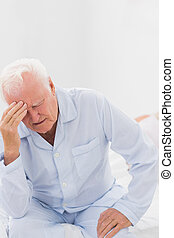 Aged man suffering while woman sleeping on the bed