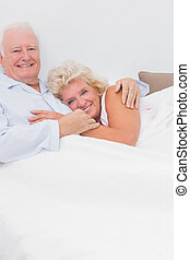 Smiling couple lying on the bed and embracing