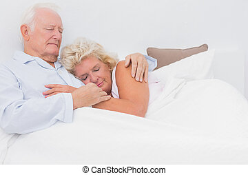 Asleep couple lying on the bed and embracing