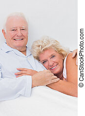 Happy couple lying on the bed and embracing