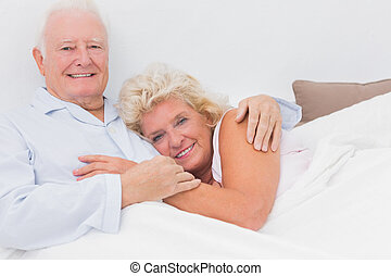 Cheerful couple lying on the bed and embracing