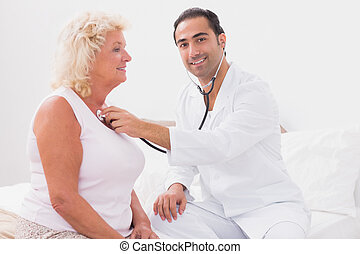 Smiling doctor examining an old woman at home