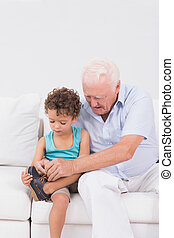 Grandson tying his shoelaces with his grandfather sitting on...