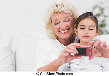 Granddaughter and grandmother taking pictures on the sofa