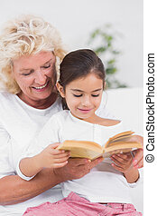 Granddaughter and grandmother reading a novel together on...
