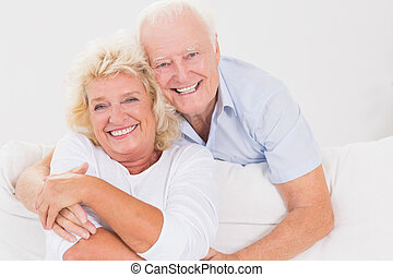Old couple hugging sitting on the sofa