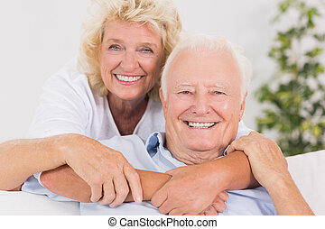 Happy old couple portrait hugging on the sofa