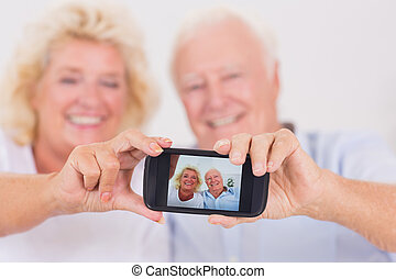 Old couple taking pictures with a smartphone at home