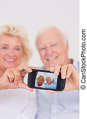 Aged couple taking pictures with smartphone - Aged couple...