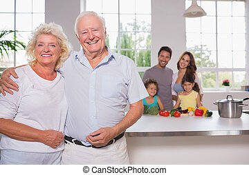 Grandparents in front of their family in the kitchen