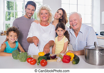 Multi-generation family cutting vegetables together in the...