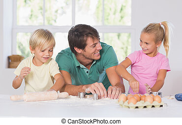 Father and his children cutting cookies out in the kitchen