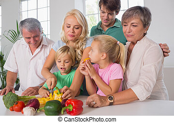 Mother chopping peppers for family in kitchen