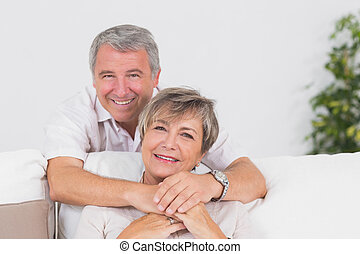 Portrait of smiling old lovers in sitting room