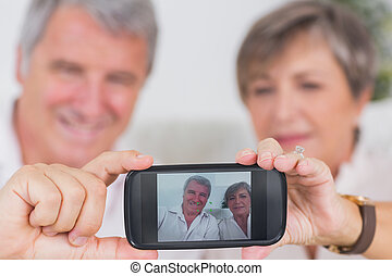 Old couple taking a picture of themselves on a smartphone