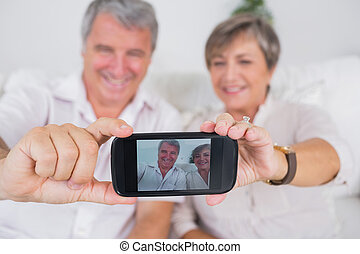Old lovers taking a picture of themselves with smartphone