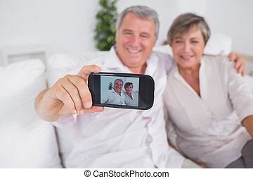 Old man taking a photo of him and his wife with a smartphone
