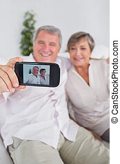 Old man taking a picture of him and his wife with a...