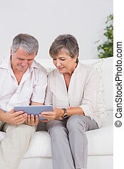 Old couple looking tablet pc with smiling - Old couple...