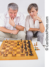Old couple playing chess in sitting room