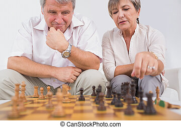 Old lovers playing chess in sitting room
