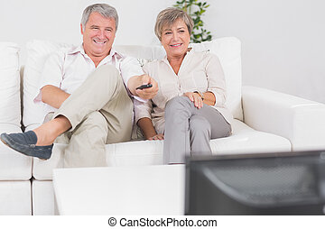 Old couple watching TV with legs crossed in sitting room