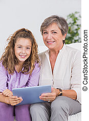 Child and her grandmother looking at the camera with tablet...