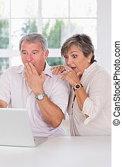 Old couple shocked in front of a laptop together in kitchen