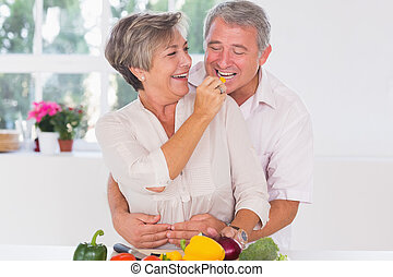 Old man tasting vegetable held by wife in kitchen