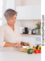 Old woman cutting vegetables on a cutting board in kitchen
