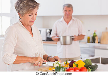 Old couple preparing food in kitchen