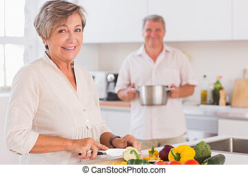 Old couple smiling preparing food in kitchen